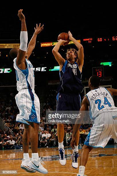 Dirk Nowitzki of the Dallas Mavericks makes a shot over David West and Morris Peterson of the New Orleans Hornets at New Orleans Arena on November 4...