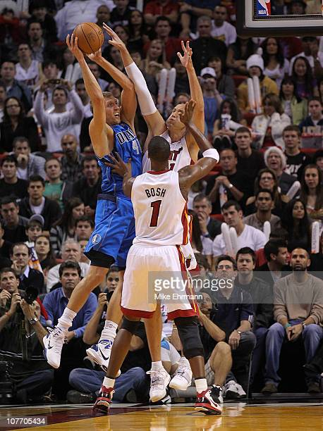Dirk Nowitzki of the Dallas Mavericks passes over Chris Bosh and Zydrunas Ilgauskas of the Miami Heat during a game at American Airlines Arena on...
