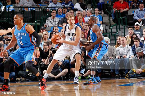 Dirk Nowitzki of the Dallas Mavericks posts up against Serge Ibaka of the Oklahoma City Thunder on March 25 2014 at the American Airlines Center in...