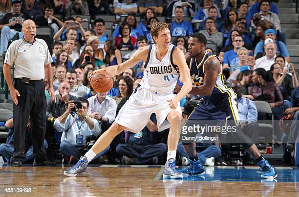 Dirk Nowitzki of the Dallas Mavericks posts up against Trevor Booker of the Utah Jazz on October 30 2014 at the American Airlines Center in Dallas...