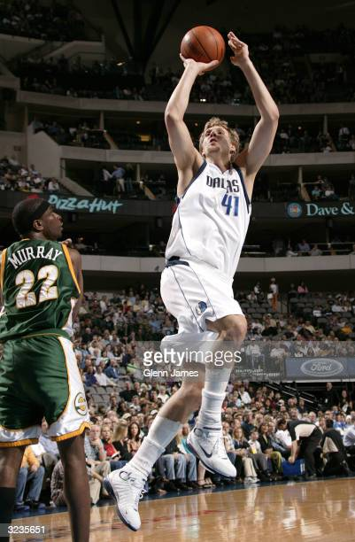 Dirk Nowitzki of the Dallas Mavericks shoots against Ronald Murry of the Seattle SuperSonics on April 6 2004 at the American Airlines Center in...