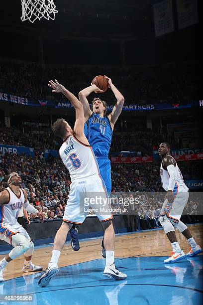 Dirk Nowitzki of the Dallas Mavericks shoots against Steve Novak of the Oklahoma City Thunder on April 1 2015 at the Chesapeake Energy Arena in...