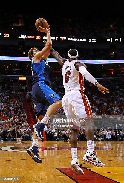 Dirk Nowitzki of the Dallas Mavericks shoots over LeBron James of the Miami Heat during a game at American Airlines Arena on January 2 2013 in Miami...