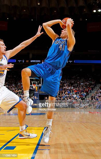 Dirk Nowitzki of the Dallas Mavericks shoots the ball against David Lee of the Golden State Warriors on March 16 2011 at Oracle Arena in Oakland...