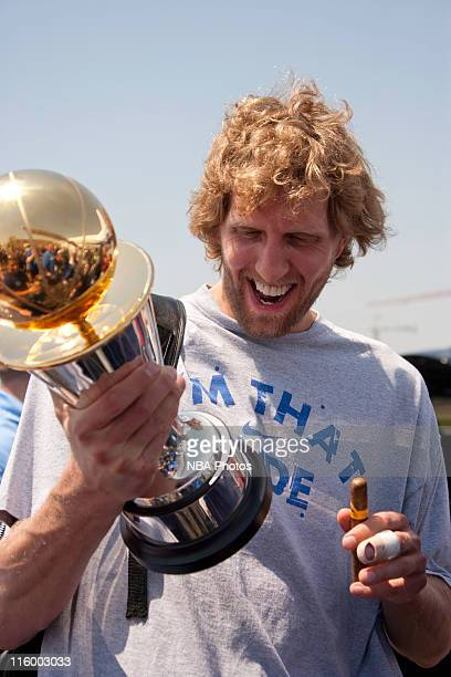 Dirk Nowitzki of the Dallas Mavericks shows off his Bill Russell NBA Finals MVP trophy as the Mavs are greeted by thousands of fans after winning the...