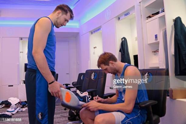 Dirk Nowitzki of the Dallas Mavericks signs his sneakers for Luka Doncic in the locker room after the game against the Phoenix Suns on April 9 2019...
