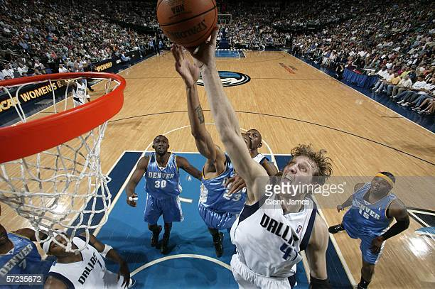 Dirk Nowitzki of the Dallas Mavericks tries for a rebound against the Reggie Evans and Carmelo Anthony of the Denver Nuggets on April 2 2006 at...