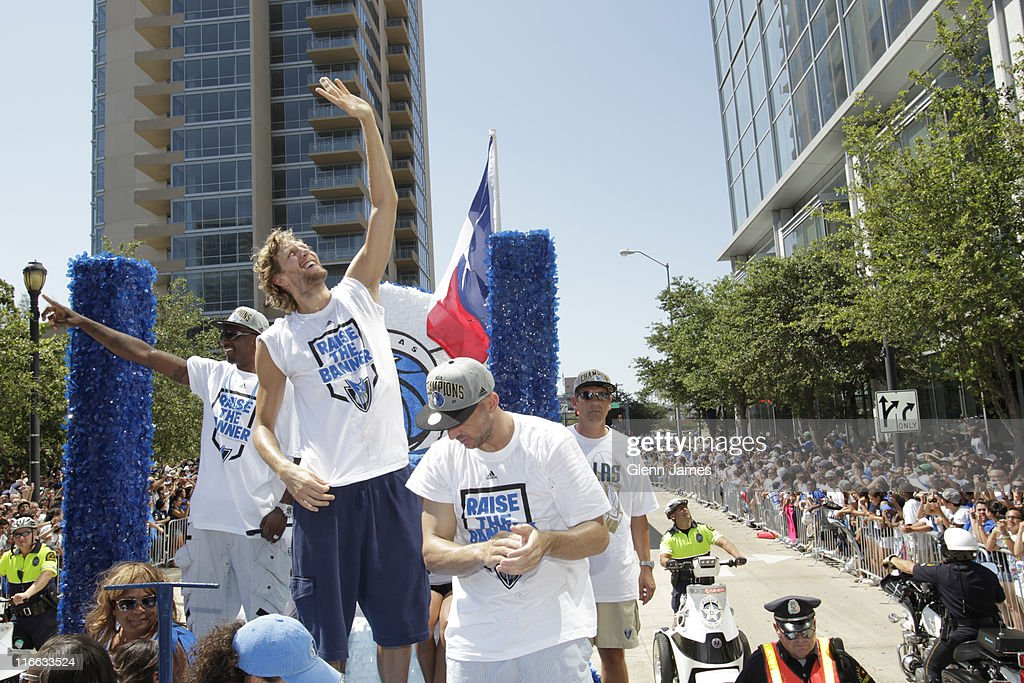 Dirk Nowitzki of the Dallas Mavericks waves to fans high and low along the route during the Mavericks NBA Champion Victory Parade on June 16, 2011 at the American Airlines Center in Dallas, Texas.