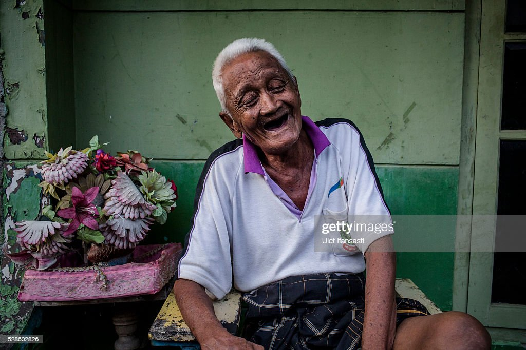 Dirman, 95 years old, laughs while telling his story as sits infront his house on May 05, 2016 in Kendal, Central Java. Dirman, was a worker, who spent 10 years imprisoned without trial for suspected ties to the Indonesian Communist Party (PKI). Survivors of Indonesia's anti-communist massacres in 1965 called for investigations on the country's purges, in which hundreds of thousands of people are believed to have been killed by the Indonesian military when the Cold War was escalating in Southeast Asia. Based on human rights groups, half a million people died in 1965 during a massacre carried out by the military and religious groups after an attempted coup by suspected communists, where an officer-led group kidnapped and executed six generals on the night of Septemeber 30, 1965. Known as one of the worst mass atrocities of the 20th century, many among the dead had no connection to Communism, and hundreds of thousands had been held in dentention centers for years during the period.