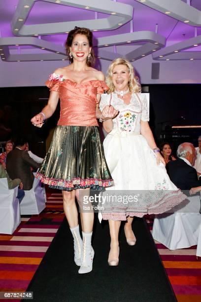 Dirndl designer Lola Paitinger and German singer Marianne Hartl walk the runway during the Kempinski Fashion Dinner on May 23 2017 in Munich Germany