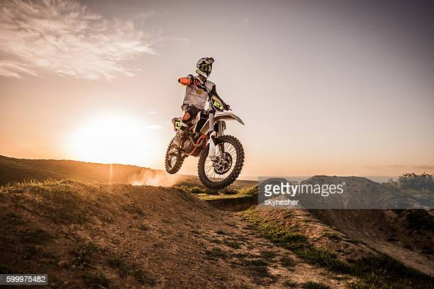 Dirt bike racer at sunset performing jump on dirt road.