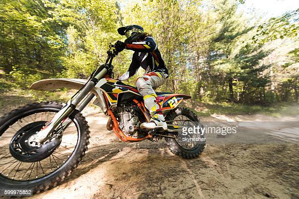 Dirt bike racer in action on extreme terrain in forest.