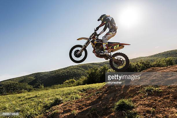 Dirt bike racer jumping while riding downhill on dirt road.