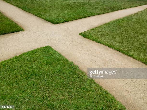 dirt crossroad surrounded by grass - crossroad stock pictures, royalty-free photos & images