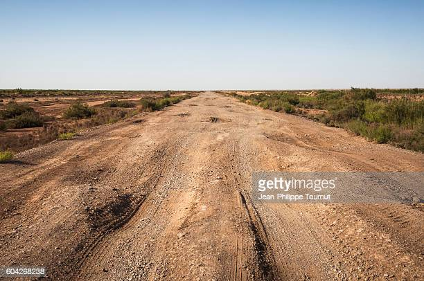 dirt road across the desert in turkmenistan, central asia - sinkhole stock photos and pictures