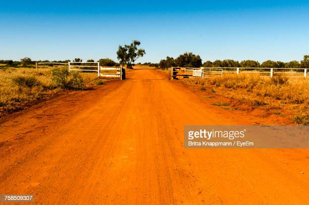 Dirt Road Along Landscape Against Clear Sky