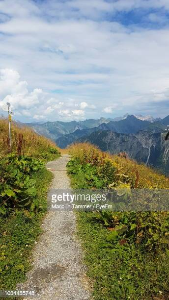Dirt Road Along Plants And Mountains Against Sky