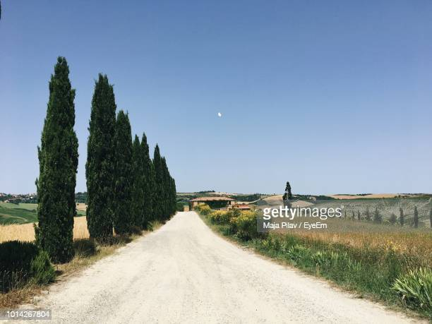 dirt road amidst field against clear sky - san quirico d'orcia stock pictures, royalty-free photos & images