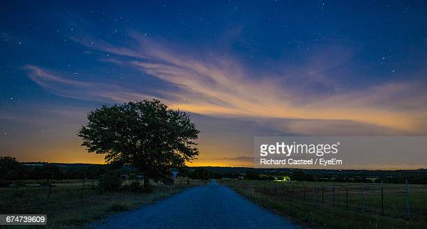 Dirt Road Amidst Field Against Cloudy Sky At Dusk