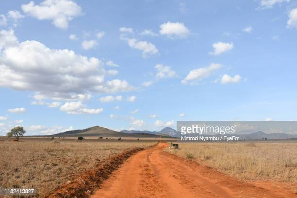 dirt road amidst field against sky - semi arid stock pictures, royalty-free photos & images
