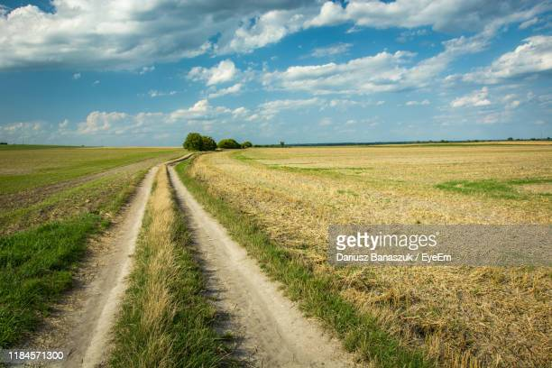 dirt road amidst field against sky - poland stock pictures, royalty-free photos & images