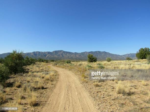dirt road amidst landscape against clear blue sky - semi arid stock pictures, royalty-free photos & images