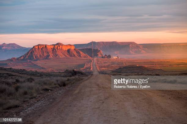 dirt road amidst landscape against sky during sunset - tranquil scene stock pictures, royalty-free photos & images