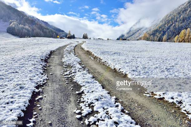 dirt road at winter valley, swiss alps - jahreszeit stock-fotos und bilder