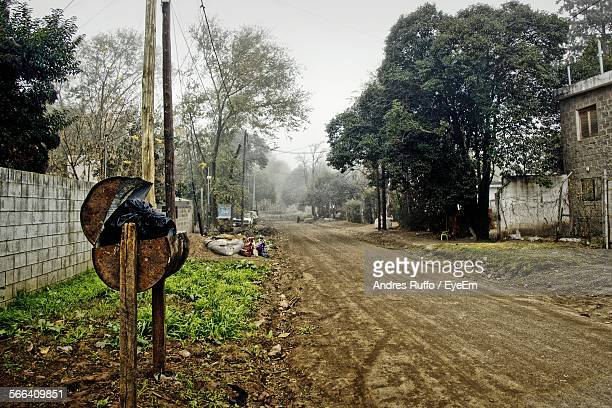 dirt road by trees in village - andres ruffo stock photos and pictures