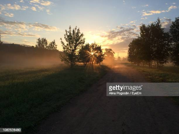 Dirt Road By Trees On Field Against Sky At Sunset
