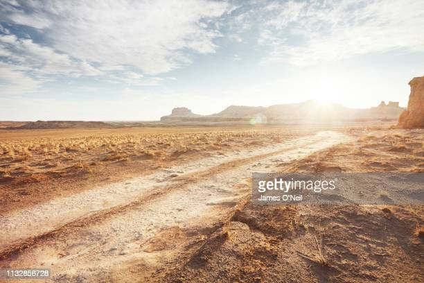 dirt road in arid desert landscape with distant cliffs and sunlight - extreme terrain stock pictures, royalty-free photos & images