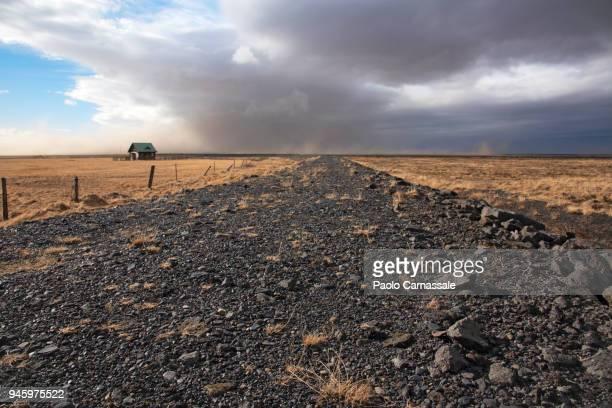 dirt road in iceland with small cottage. - terreno accidentato foto e immagini stock