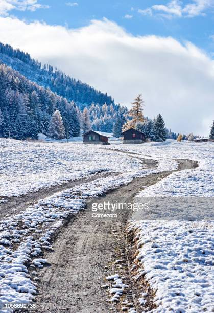 dirt road in the snow ground, european alps - extreme terrain stock pictures, royalty-free photos & images