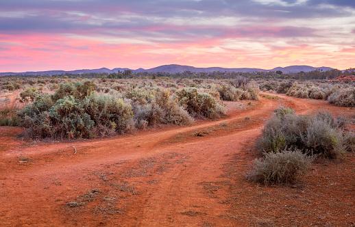 Dirt road leading across desert plains to ranges 997424672
