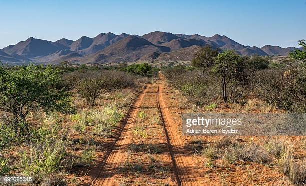 Dirt Road On Field Towards Mountains Against Clear Blue Sky