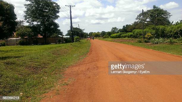 dirt road passing through village - gulu stock photos and pictures