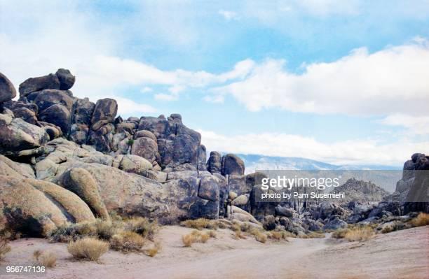dirt road through alabama hills rock formations - extremlandschaft stock-fotos und bilder