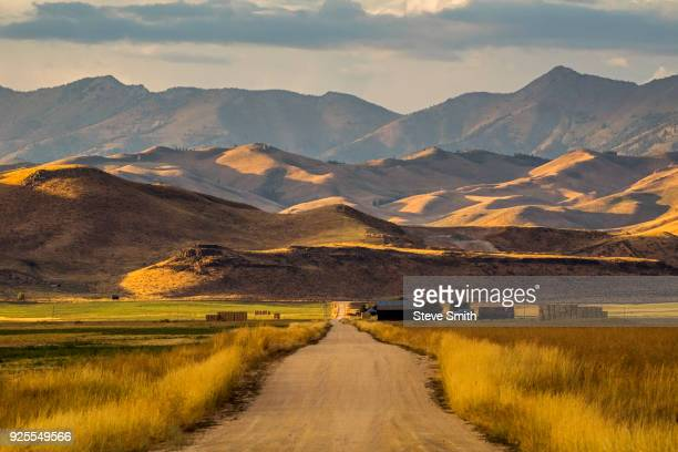 dirt road to farm and mountains - idaho stock pictures, royalty-free photos & images
