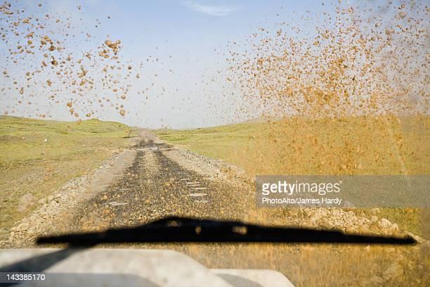 Dirt road viewed through muddy car windshield