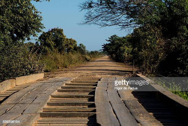 dirt roads and wooden bridges the wetland landscape - cuiabá stock photos and pictures