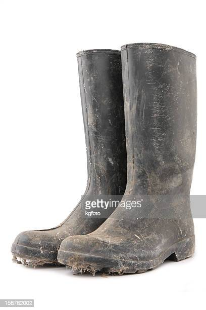 Dirty black gumboots on white background