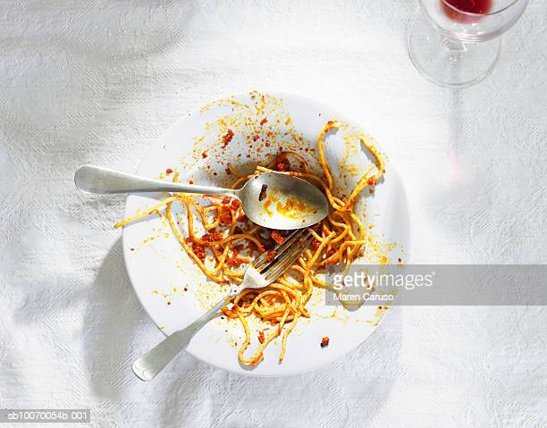 Dirty bowl with pasta leftovers with spoon and fork