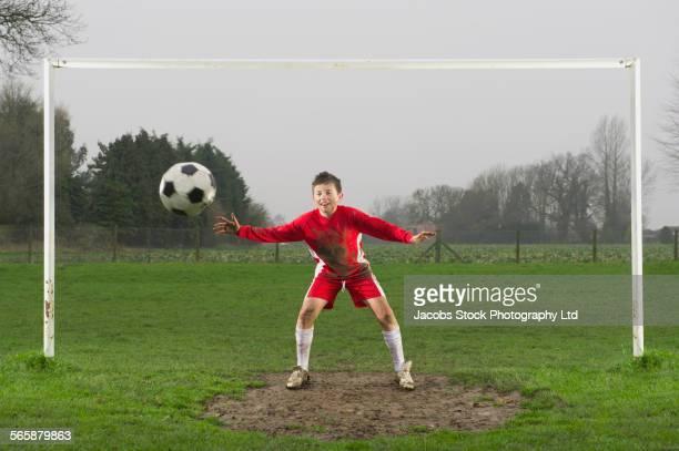 Dirty Caucasian boy guarding goal in soccer field