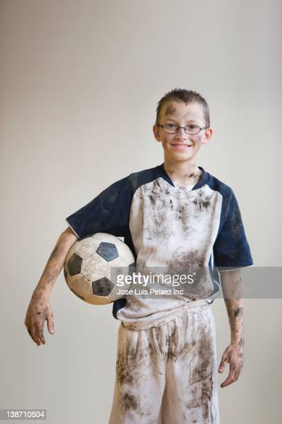 dirty caucasian boy holding soccer ball - football strip stock pictures, royalty-free photos & images
