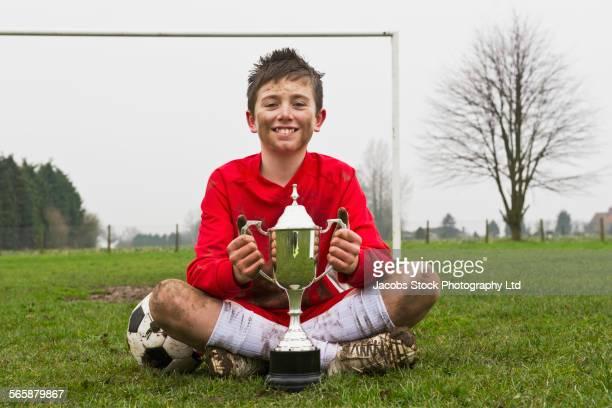 Dirty Caucasian boy holding trophy on soccer field