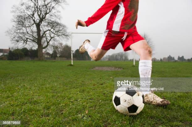 Dirty Caucasian boy kicking soccer ball on field