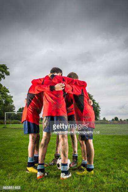 dirty caucasian soccer team talking in huddle on field - spalding england stock photos and pictures