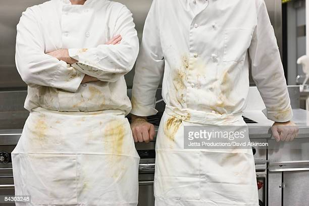 Dirty chefs leaning against stove