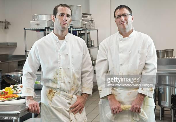 Dirty chefs posing in kitchen