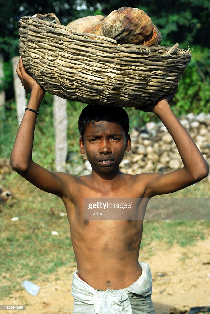 Dirty child carrying items gathered in third world country : Stock Photo